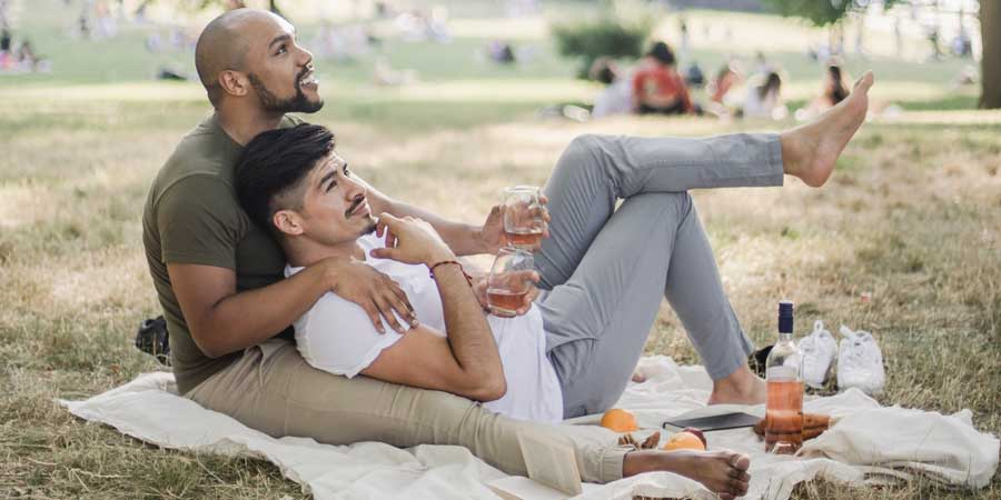 affectionate gay couple cuddle on picnic blanket in a park